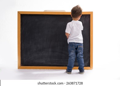 four year old boy draws with chalk on the blackboard