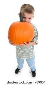 Four year old boy holding pumpkin.