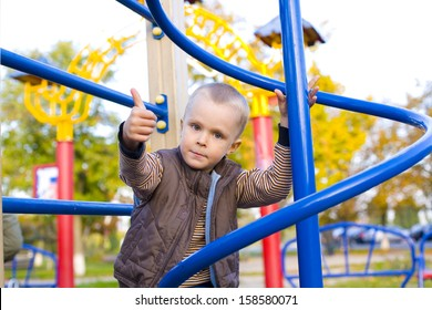 Four year old boy playing on the playground in autumn