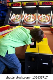 A four year old boy reaches for a ball to play skee ball