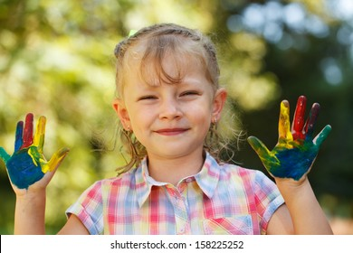 Four year old girl with hands painted in colorful paints ready for hand prints