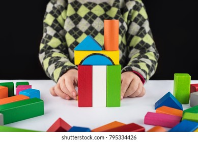 Four year old girl plays in the designer on the table. Wooden toys, colorful children's designer, black background, entertainment with a kid, development of preschoolers, construction, game