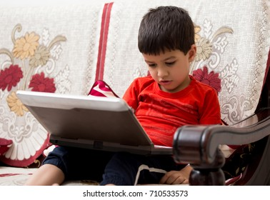 A four year old Tech savvy Indian kid playing and learning on his toy laptop