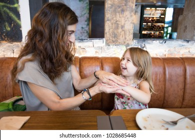 Four years age blonde girl, happy playing with hands and laughing with woman mother sitting in brown leather sofa at restaurant