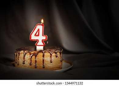 Four years anniversary. Birthday chocolate cake with white burning candle in the form of number Four. Dark background with black cloth