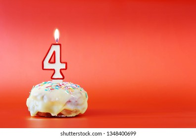 Four years birthday. Cupcake with white burning candle in the form of number 4. Vivid red background with copy space
