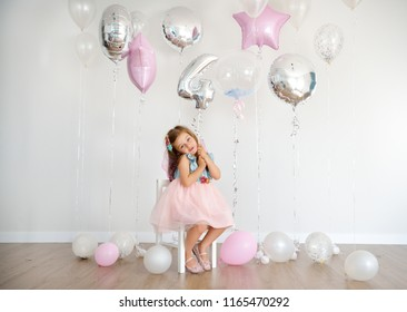 Four years old Birthday party. Cute little girl in the room decorated with balloons.