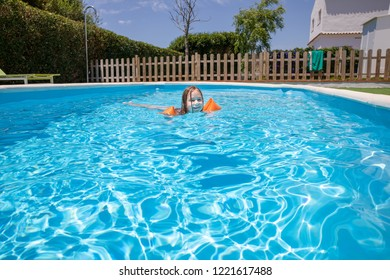 four years old blonde child with orange floater sleeves in arms, armbands, smiling face swimming in blue water of pool