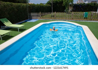 four years old blonde child with orange floater sleeves in arms, armbands, swimming in blue water of swimming pool with face expression: danger, diving, jump…