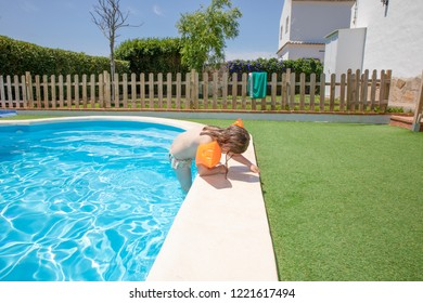 four years old blonde child with orange floater sleeves in arms, armbands, coming out of the swimming pool by the curb