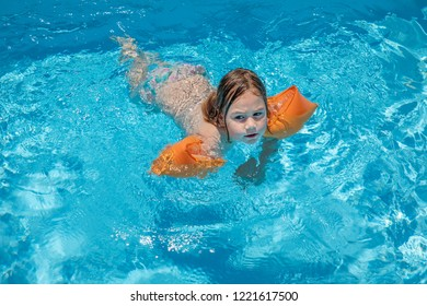 four years old blonde child with orange floater sleeves in arms, armbands, swimming in blue transparent water of pool