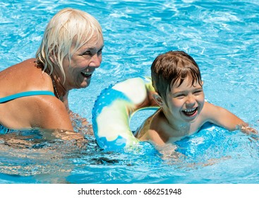 Four years old boy with his Grandmother in a swimming pool. Woman is sixty three/Water games with Grandma