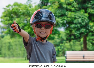 A four years old boy wearing sunglasses, a bike helmet and  stands in a sunny park with trees and blue sky in the background.