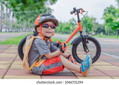 A four years old boy wearing sunglasses and safety helmet sitting on the floor and a backpack in a sunny park