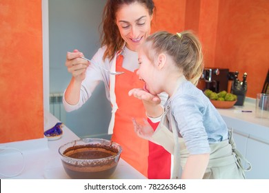 four years old girl licking or sucking cream from mother hand, both with apron making and cooking a sponge chocolate cake at kitchen home, together in teamwork