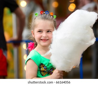 Four years old  girl with white cotton candy.