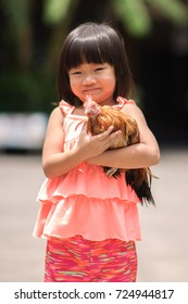 Four years old happy asian girl smiling and enjoying with chicken care.