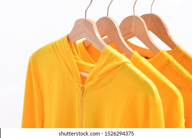 Four yellow knitted , hoodie ,sweater are hanging on Clothes Hanger,