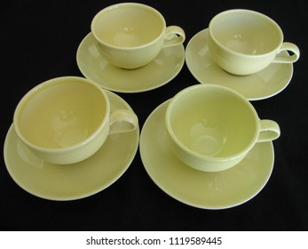 Four yellow mid century modern ceramic coffee cups and saucers on a black limbo background are a retro vintage image