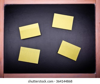 four yellow papers on an old black chalkboard