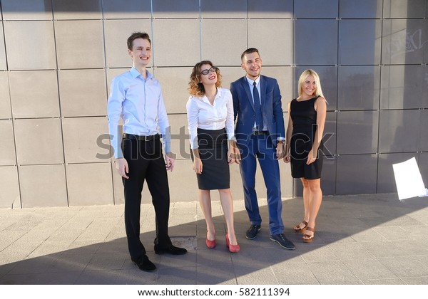 Four young adult elegant people, two women and two men students, prospective entrepreneurs  scatter paper and rejoice success, implementation of annual of business plan, the end of working da