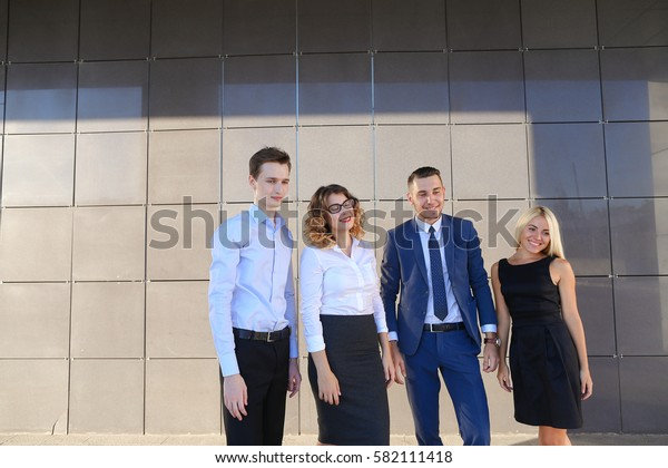 Four young adult elegant people, two women and two men students smiling, posing at camera and standing of business center outdoors. One of guys dressed in blue classic suit, white shirt with tie