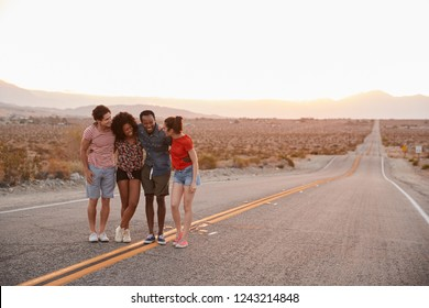 Four young adult friends standing on desert highway talking