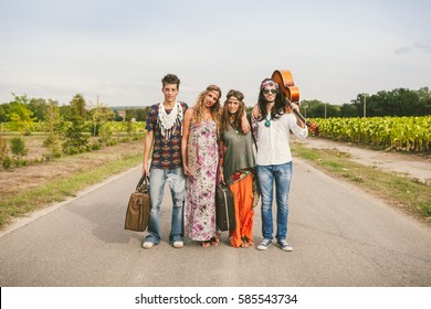 Four young adult hippie friends standing in the middle of a road