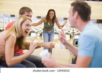 Four young adults laughing and gesturing in a bowling alley