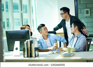 four young asian business people conversing in office, happy and relaxed.