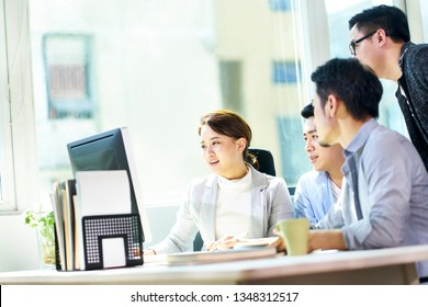 four young asian businesspeople meeting in office discussing business plan using desktop PC.