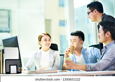 four young asian businesspeople meeting in office discussing business plan using tablet PC.