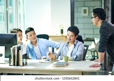 four young asian corporate executives working together discussing business plan in office.