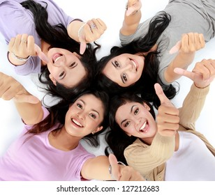 four young attractive asian women relaxing smiling lying on the floor showing thumbs up