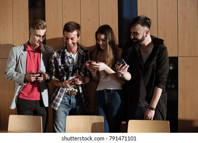 Four young and attractive people having fun with their gadgets. People holding phones in their hands and talking.