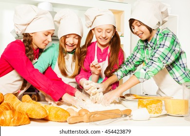 Four young bakers kneading dough at the kitchen