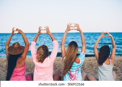Four young beautiful girl hats sit on the beach