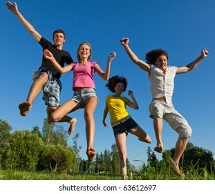 Four young boys and girls jumping on a background of blue sky