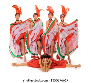 Four young cancan dancers girls lift up skirts flirting on a white background with one girl doing twine on the floor