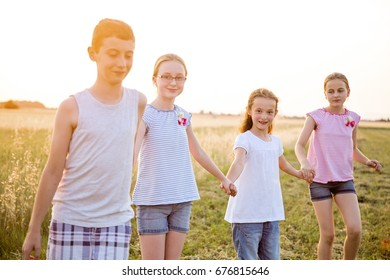 Four young caucasian kids holding hands, walking at cultivated countryside field, at summer sunset, wearing casual summer clothes