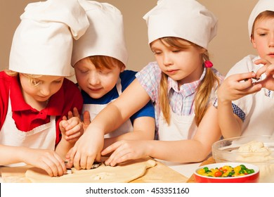 Four young chefs having fun making homemade cookie