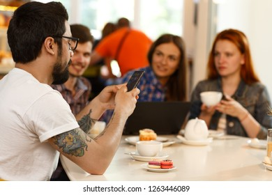 Four young colleagues working, sitting together during the coffee break at bakery shop with dessert on table. Man with modern tattoo using smartphone while other listen him. Concept of teamwork.
