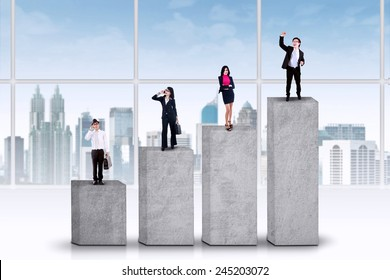 Four young entrepreneurs standing on business chart, symbolizing their achievement