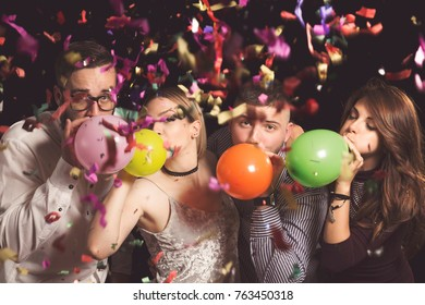 Four young friends at New Year's Eve party at midnight blowing colorful balloons and having fun
