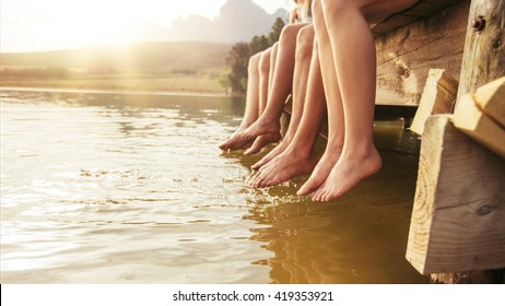 Four young friends sitting on jetting with their legs hanging down to the water on a summer day. Focus on legs of young people.