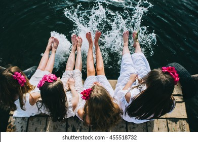 Four young girls friends sitting on a jet with legs hanging down to the water on a summer day