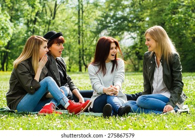 Four young girls sitting in the park and talking.Did you hear?!