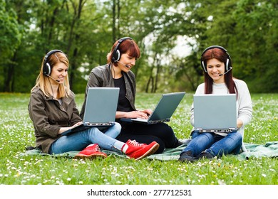 Four young girls sitting in the park and using laptop.Happy girls using laptop