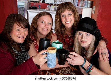 Four young happy female friends at a cafe