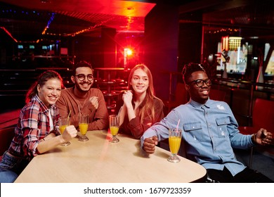 Four young happy intercultural bowling fans sitting by table while having fresh orange juice and looking at players on alleys